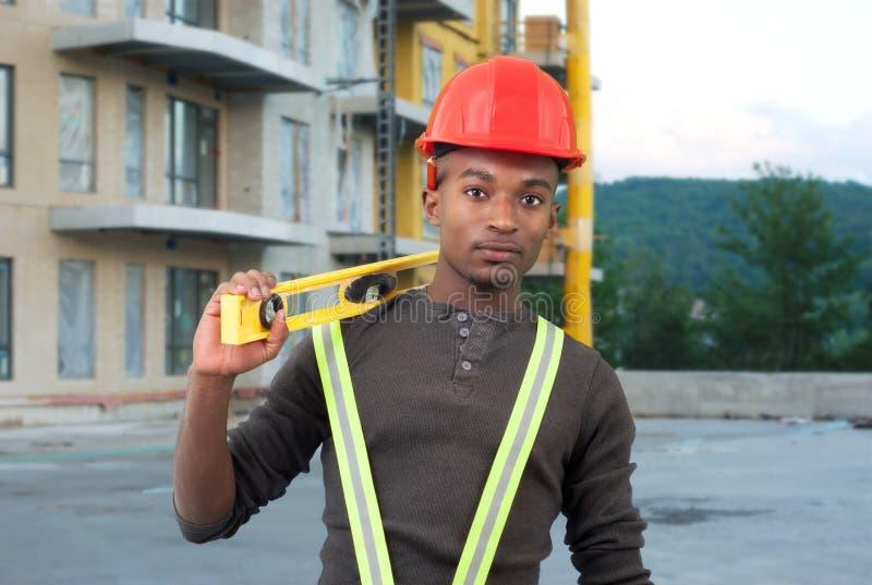 Pracownika budowlanego mienia pozioma narzędzie z czerwonym zbawczym kapeluszem zdjęcie stock