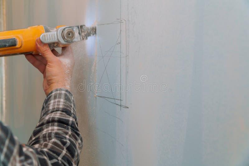 Pracownika budowlanego tnący gipsowy plasterboard używać elektrycznego krajacza kąta ostrzarza obrazy stock