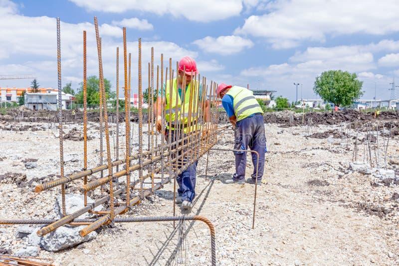 Pracownika budowlanego wiążący rebar dla wzmacnia betonową kolumnę zdjęcie stock