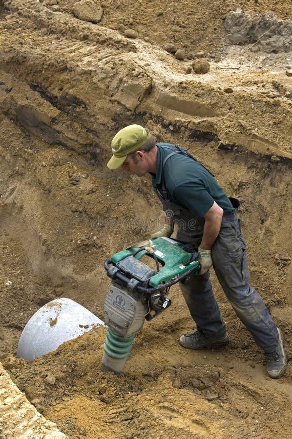 Pracownika compacting piasek z rozedrganym talerzem majstruje fotografia royalty free