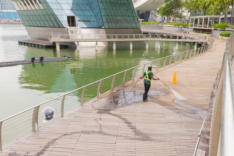 Pracownika czyści taras z władzy płuczką - wysoka woda nacisk czysty na drewnianej taras powierzchni zdjęcie royalty free