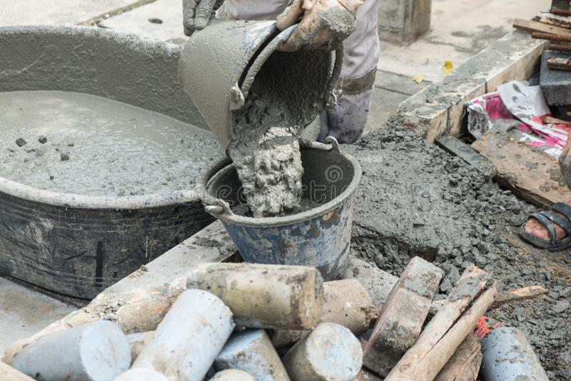 Pracownika dolewania cementu mieszanki beton w wiadrze zdjęcia stock