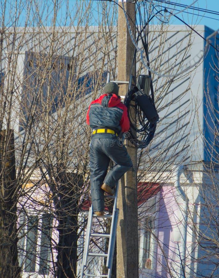 Pracownika elektryk pracuje z drutami w ulicznej pozyci na schodkach przy stosem obraz royalty free