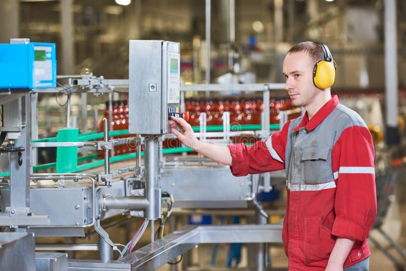 Pracownika fabrycznego operacyjny konwejer z piwnym napojem butelkuje chodzenie fotografia stock