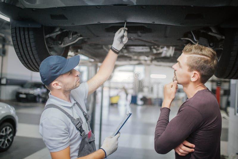Pracownika i właściciela stojaki pod samochodem Pierwszy mężczyzna jest punktem na pojazdzie Inny jeden myśleć Trzyma rękę blisko zdjęcia stock