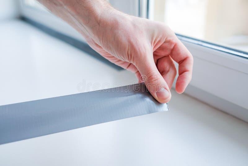 Pracownika kładzenia lakowania taśma na okno w domu obraz royalty free