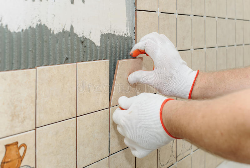 Pracownika kładzenia płytki na ścianie w kuchni obraz royalty free