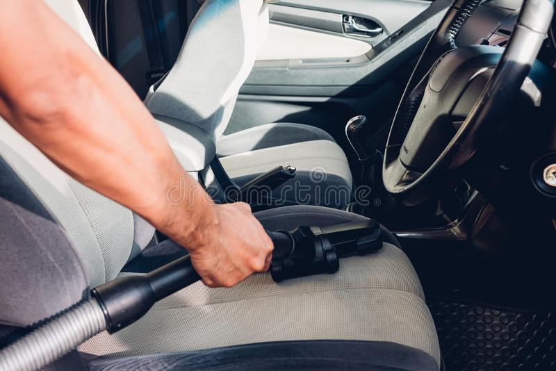Pracownika mężczyzny pyłu czyści wewnętrzna próżnia wśrodku samochodu fotografia stock