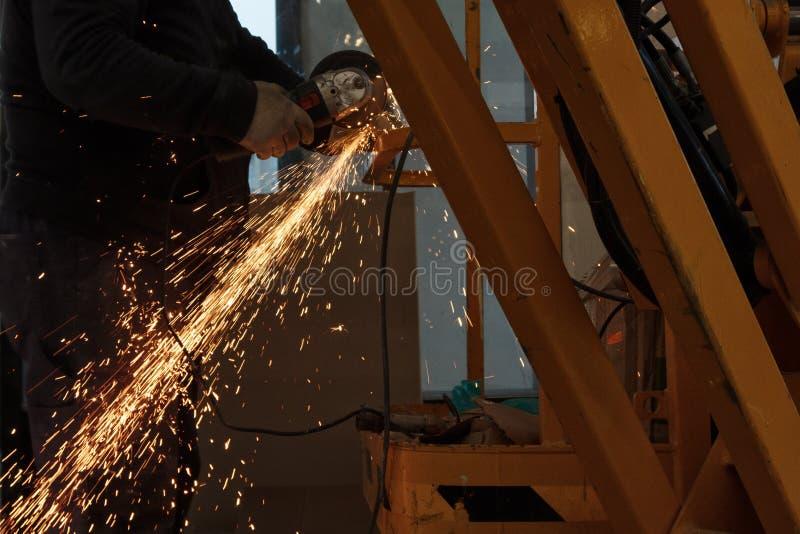 Pracownika metalu szlifierski tnący prześcieradło z ostrzarz iskrami i maszyną obraz stock
