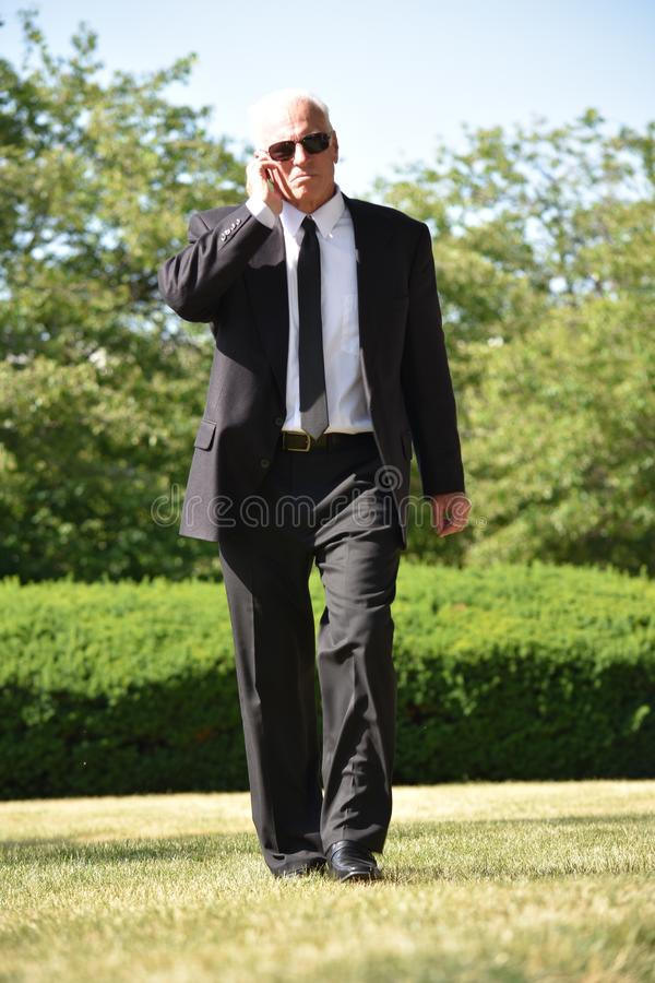 Pracownika Ochronego przesłuchanie Jest ubranym okularów przeciwsłonecznych Chodzić obrazy stock