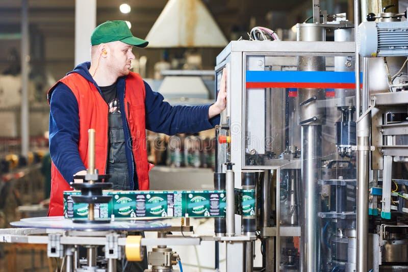 Pracownika operacyjny konwejer lub etykietowanie maszyna przy fabryką zdjęcie stock