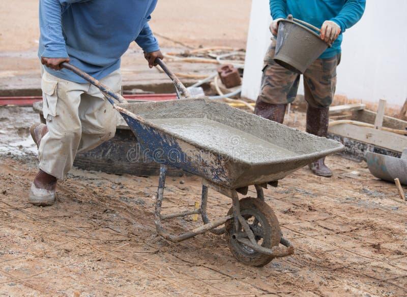 Pracownika pchać taczkowy z mokrym cementem nalewać betonowej podłoga fotografia royalty free
