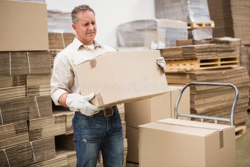 Pracownika przewożenia pudełko w magazynie zdjęcia royalty free