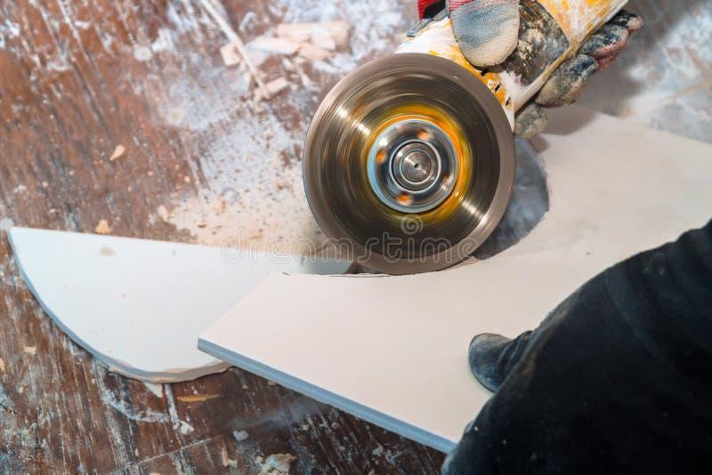 Pracownika rozcięcia ostrzarza dachówkowy używa cięcie w warstwy ceramiczne podłogowe płytki fotografia stock