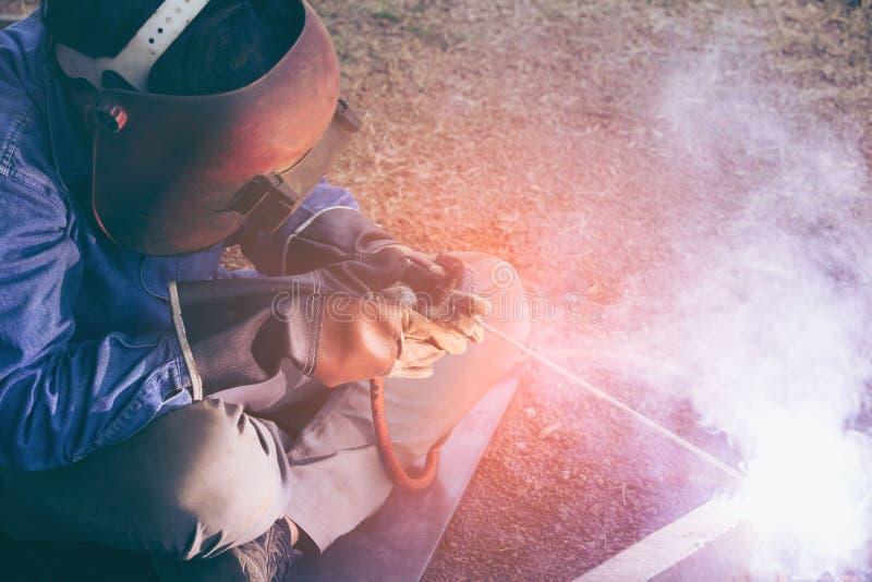 Pracownika spawacza pracująca spawalnicza stal w przemysle z bezpieczeństwo maski zbawczymi rękawiczkami i zbawczym wyposażeniem zdjęcia stock