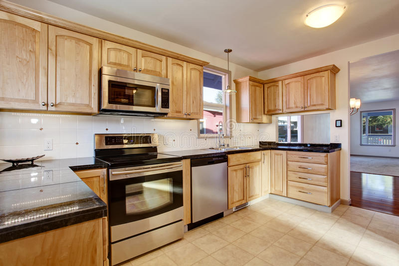 Practical kitchen room with light tones cabinets and steel appliances. Practical kitchen room with light tones cabinets, steel appliances, black granite tops stock photo