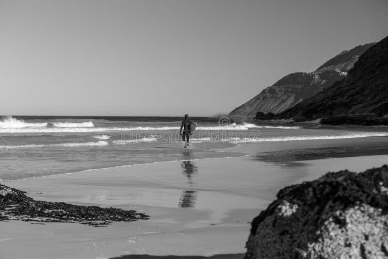 Practicando surf en la playa de Noordhoek, en Cape Town, Suráfrica fotografía de archivo libre de regalías