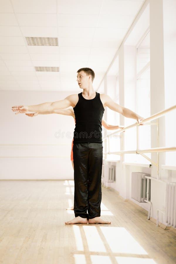 Practice in aerobics room. Heterosexual couple in sportswear stretching in aerobics room stock images