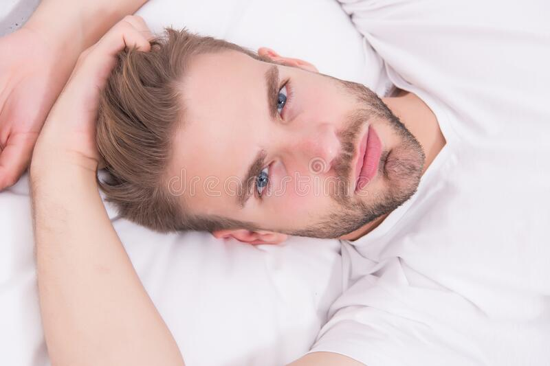 Practice calming activities such as meditation before going to bed. Healthy sleep concept. Tips promoting healthful. Sleep habits. Handsome man relaxing in bed royalty free stock image