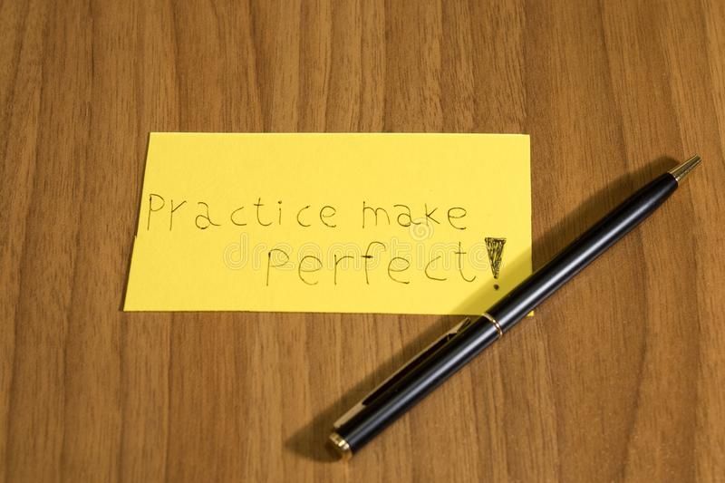 Practice makes perfect handwrite on a yellow paper with a pen on stock photos