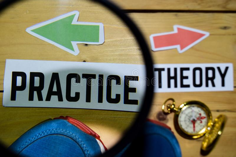 Practice or Theory opposite direction signs on magnifying with sneaker and compass on wooden. Vintage background. Business, education and finance concepts royalty free stock photo