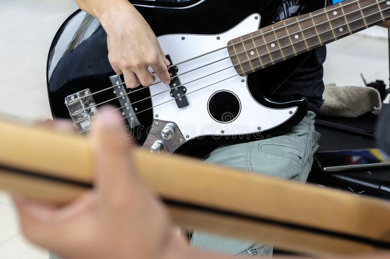 Practice your music to prepare for the show. Playing bass guitar stock photo