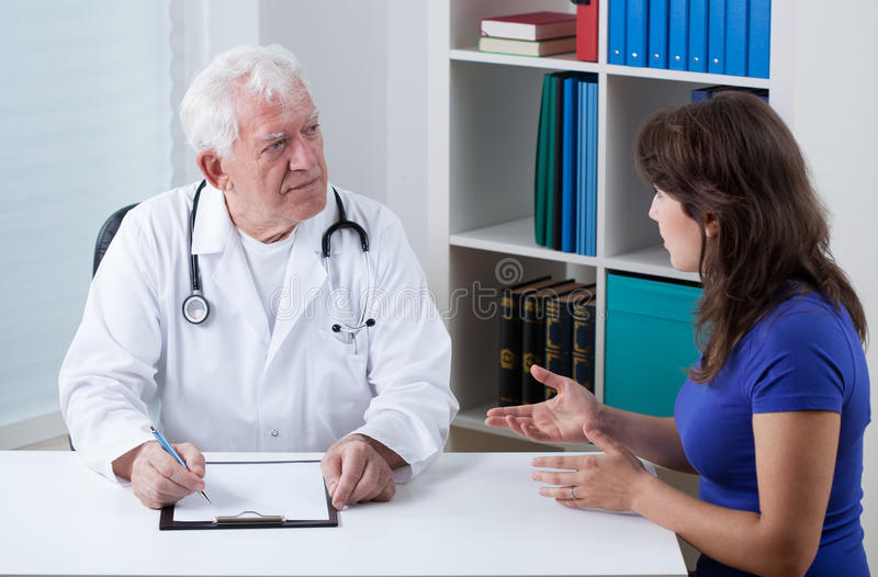 Practiced doctor talking with patient royalty free stock photos