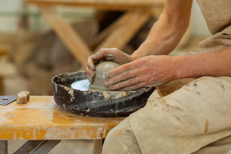 Practiced hard-working guy being an expert in pottery mastery. Producing new creation . Practiced hard-working guy being an expert in pottery mastery while using royalty free stock photo
