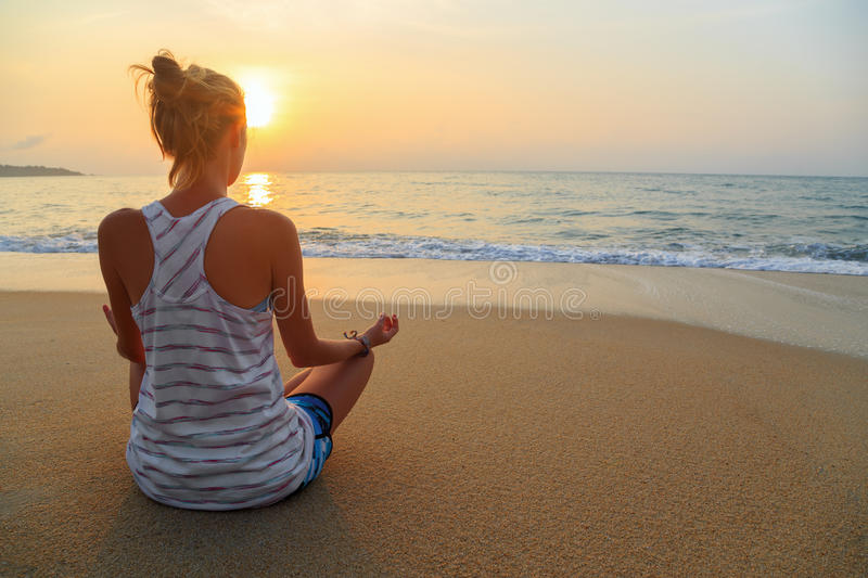 Practices meditates in sunrise stock images
