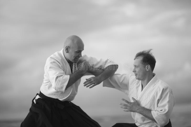 Practicing martial art. Martial arts masters demonstrating technique outside, monochrome stock images