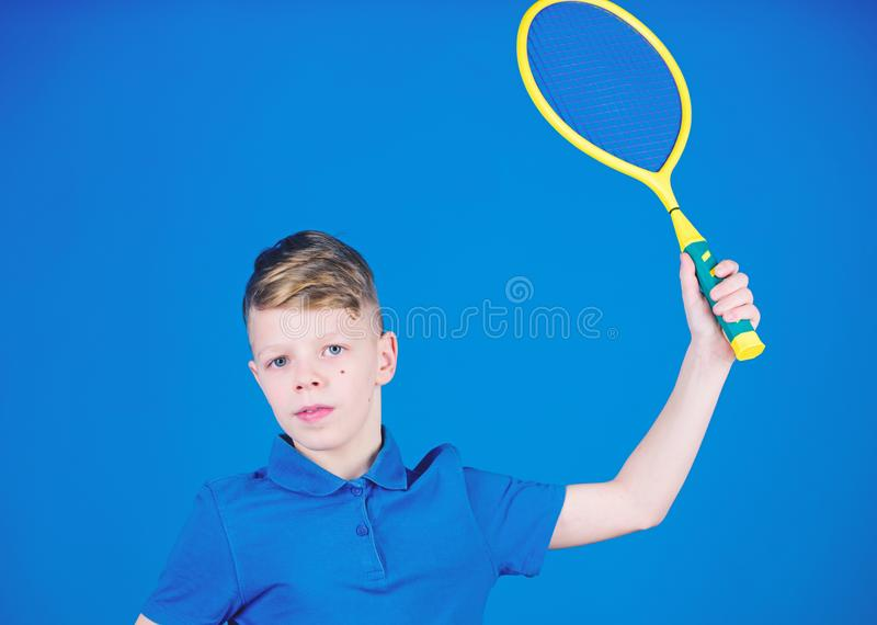 Practicing tennis skills. Guy with racket enjoy game. Future champion. Dreaming about sport career. Athlete kid tennis. Racket on blue background. Tennis sport stock image