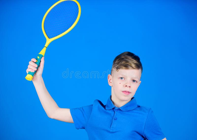 Practicing tennis skills. Guy with racket enjoy game. Future champion. Dreaming about sport career. Athlete kid tennis. Racket on blue background. Tennis sport stock photos