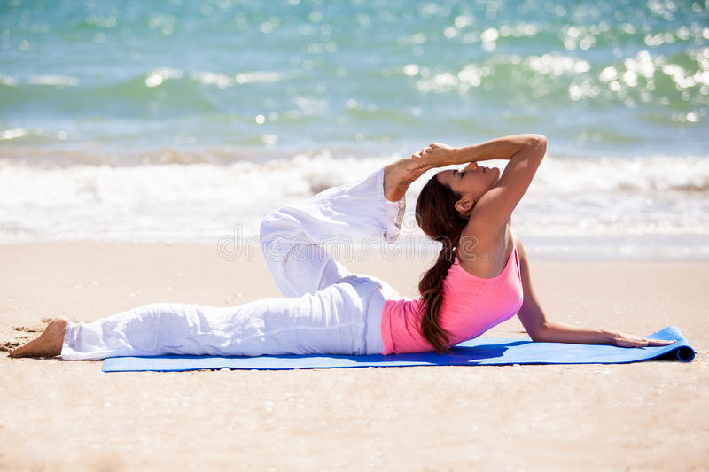 Practicing yoga at the beach. Cute flexible Latin woman stretching with a yoga pose at the beach royalty free stock photos