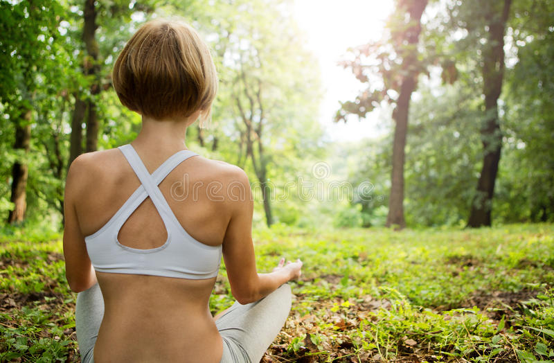 Practicing of yoga outdoors. Young woman In the lotus posture in the sunny forest. Yoga in nature. yoga poses. Girl from the back royalty free stock photos