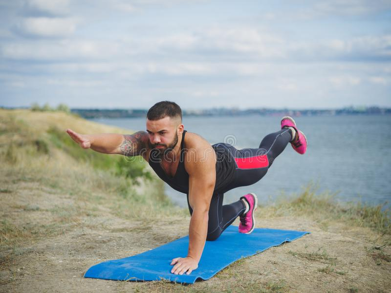 Left side of strong man practices yoga outside, near the river, on green mountain. Male training, hardowking person. Practicing yoga outside on mountain, near stock photography