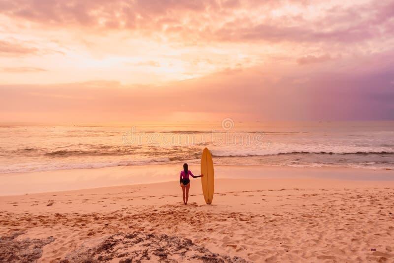 Practique surf a la muchacha en traje mojado con la tabla hawaiana que se coloca en una playa en la puesta del sol o la salida de fotos de archivo
