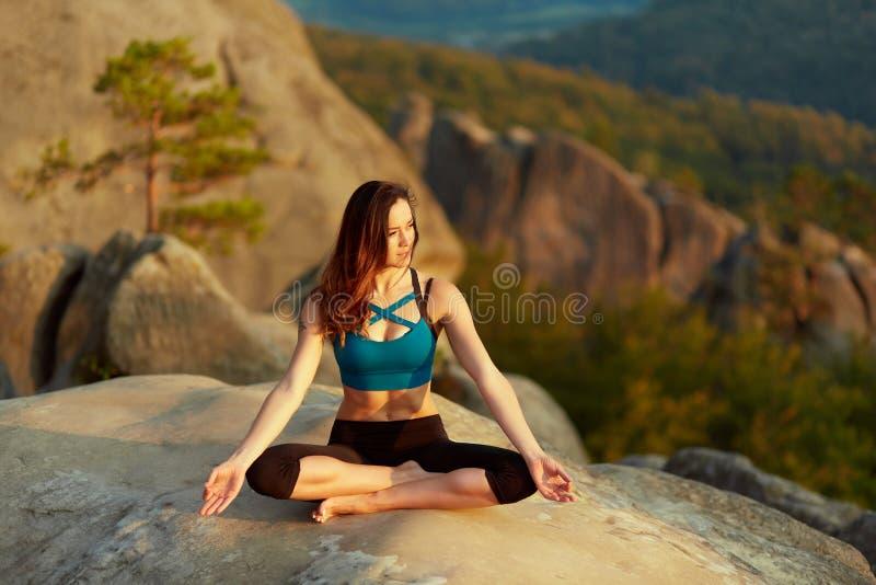 Practiving yoga för ung kvinna utomhus royaltyfri bild