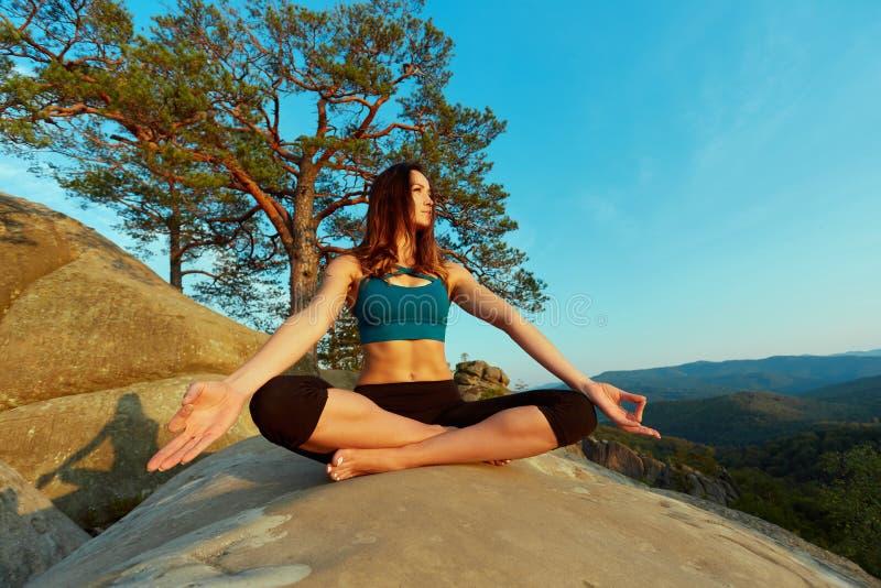 Practiving yoga för ung kvinna utomhus arkivfoto