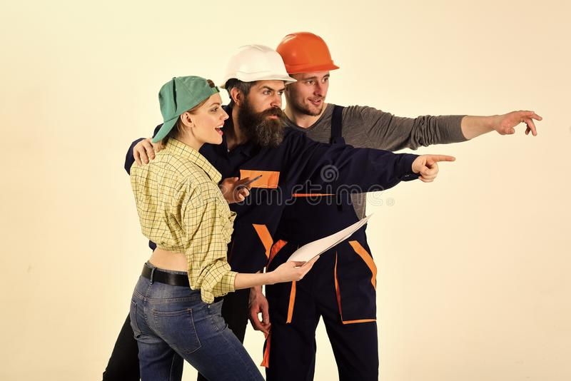 Pracująca drużyna Brygada pracownicy, budowniczowie w hełmach, naprawiacze i dama, dyskutujemy kontraktacyjnego, białego tło, bry zdjęcia stock