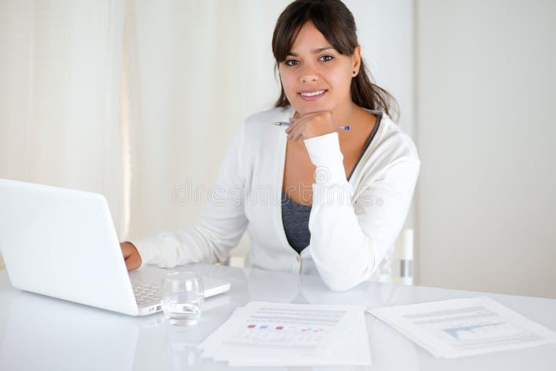 Pracująca młoda kobieta patrzeje ciebie przy biurem obrazy royalty free