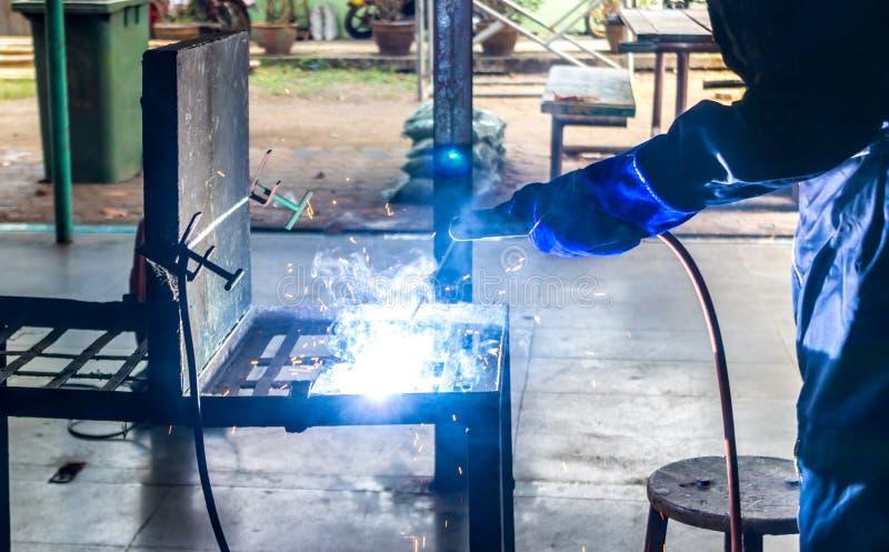 Pracująca osoba O spawacz stalowej spawalniczej maszynie obrazy royalty free