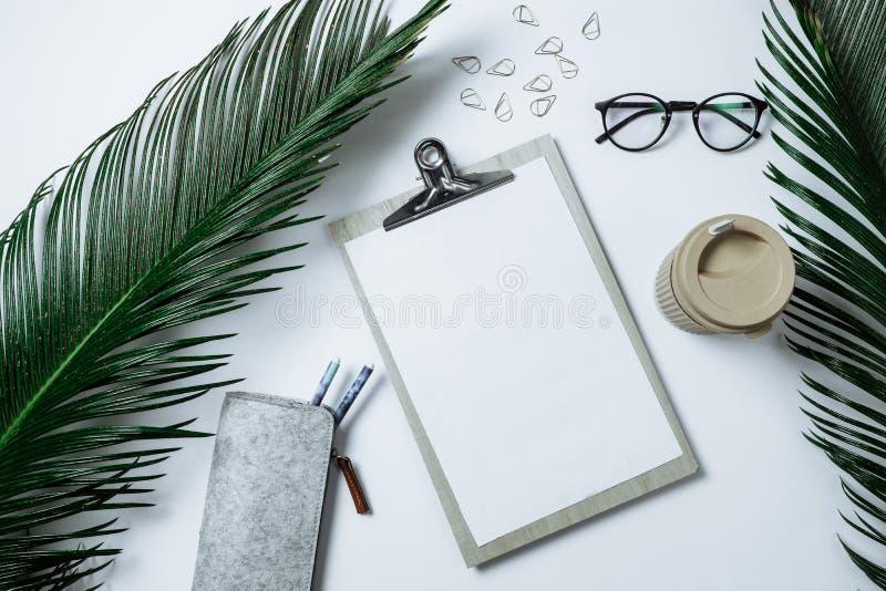 Pracująca przestrzeń: schowek, palmowy liść, kawa i kapelusz na, błękitni półdupki obraz royalty free