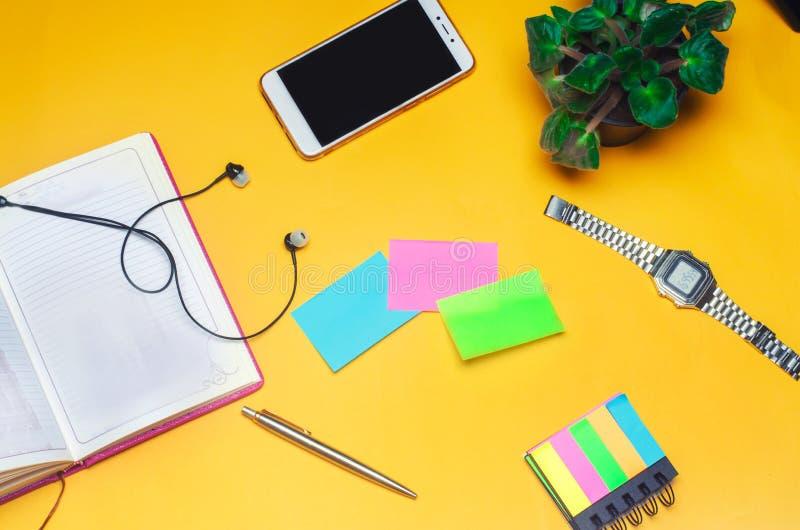 Pracująca przestrzeń z notatnikiem, pióro, zegar, telefon, hełmofony na żółtym tle miejsce tekst Pracująca przestrzeń fr zdjęcie stock