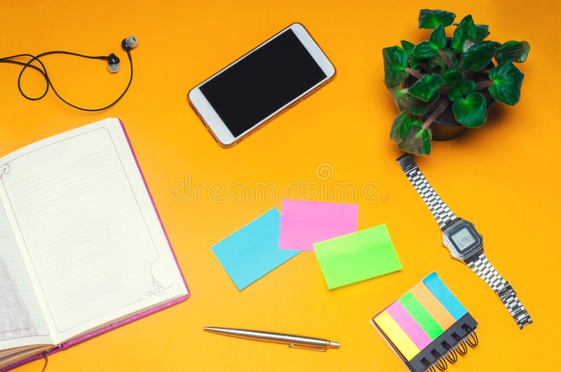 Pracująca przestrzeń z notatnikiem, pióro, zegar, telefon, hełmofony na żółtym tle miejsce tekst Pracująca przestrzeń fr zdjęcia royalty free