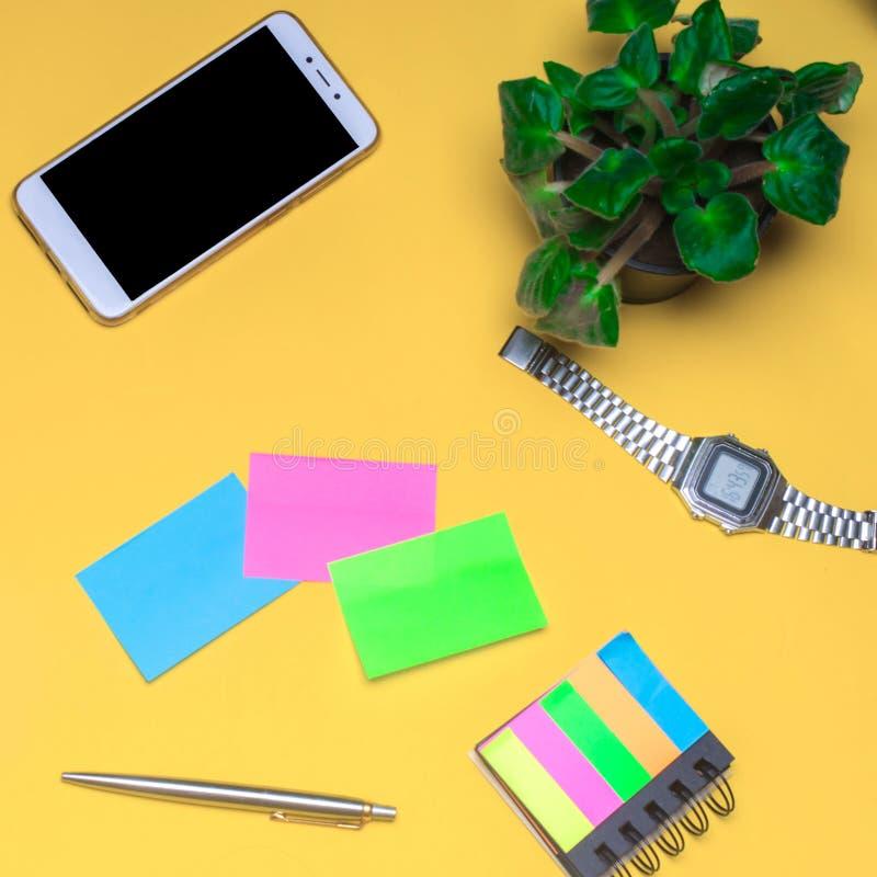Pracująca przestrzeń z zegarem, telefon, majchery, notatki na żółtym tle miejsce tekst Pracująca przestrzeń freelancer, obrazy royalty free