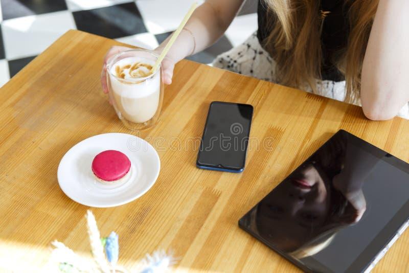 Pracujący drewniany biurko stół z notebookiem, pastylka komputer osobisty, wisząca ozdoba, ręka telefon, kawowy szklany latte fotografia stock