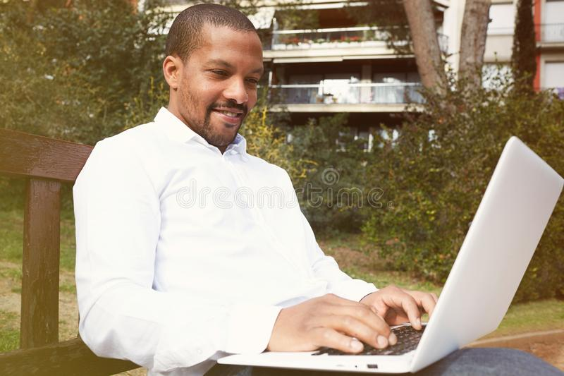 Pracujący momenty Widok młody Afrykański mężczyzna w formalwear pracuje na laptopie podczas gdy siedzący przy miasto parkiem plen zdjęcia stock