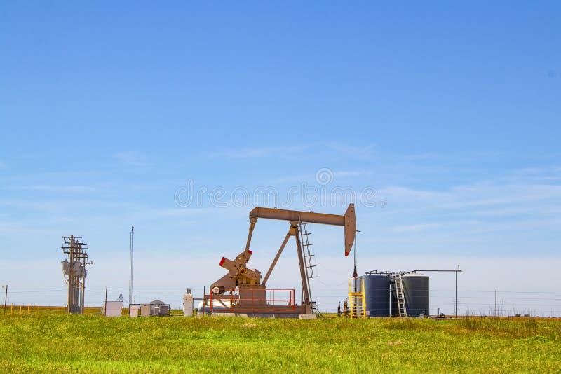 Pracujący Pompowy Jack na szybie naftowym z zbiornikami na miejscu out na horyzoncie na równinach z elektrycznymi liniami i niebi zdjęcie royalty free