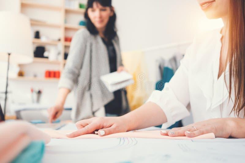 Pracujący proces dwa kobiet krawcowa w szwalnym studiu Drużyna robi ubraniowy projektant i tworzy nowej koncepci modę odziewa fotografia stock