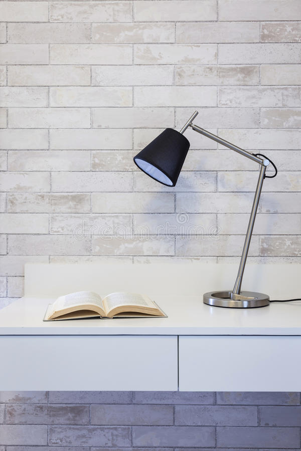 Pracujący stół i książka z lampą na ściennym tle zdjęcia stock